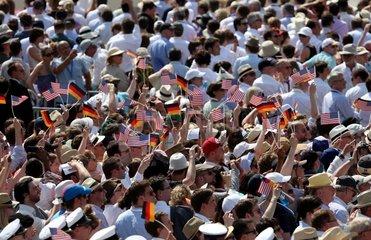 Zuschauer mit Faehnchen der USA und Deutschlands vor dem Brandenburger Tor in Berlin