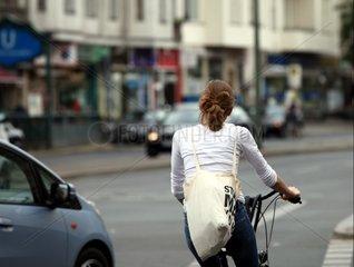 Junge Frau auf Fahrrad im Strassenverkehr