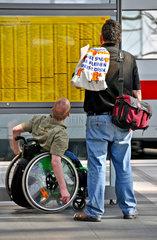 Rollstuhlfahrer liest Bahnfahrplan