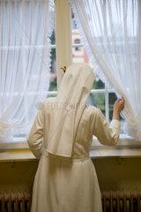 Heitersheim  Deutschland  eine Schwester schaut aus dem Fenster