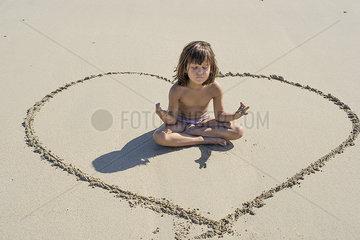 Little girl meditating on beach