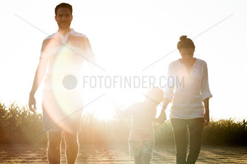 Family with little boy walking together outdoors
