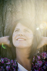 Woman leaning against tree trunk  smiling cheerfully