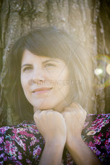 Woman leaning against tree trunk  smiling  portrait