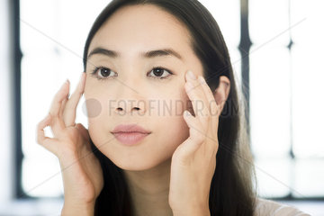 Woman holding finger tips on face