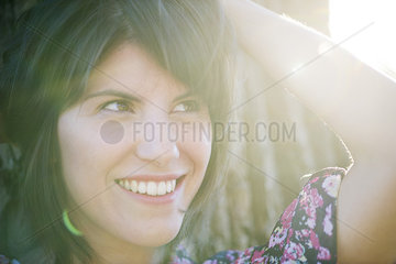 Woman smiling dreamily outdoors  portrait