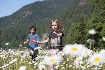 Children running in field of daisies