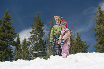 Young siblings standing together in snow