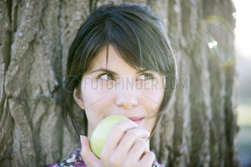 Woman eating apple  looking up thoughtfully