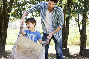 Man teaching young son how to use wheelbarrow
