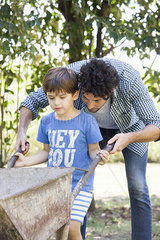 Man teaching young son how to use wheelbarrow