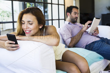 Couple using wireless devices at home