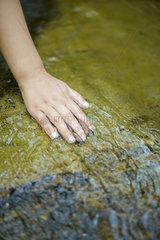 Hand touching rock in stream