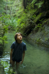 Boy wading in stream  looking up in awe
