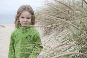 Girl behind dune grass at beach  portrait
