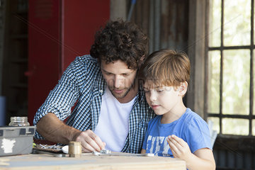 Child helping his father in workshop