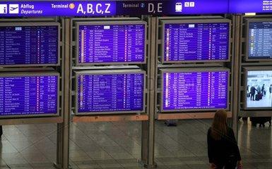 Frau vor Informationstafel am Frankfurter Flughafen