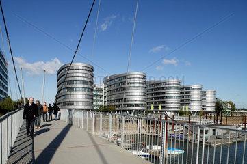 Duisburg  Deutschland  Passanten auf der Buckelbruecke  im Hintergrund der Buerokomplex Five Boats