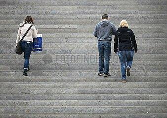 Drei Personen gehen eine Treppe hinauf