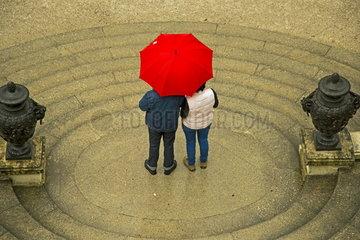 Ein Ehepaar unter einem roten Regenschirm