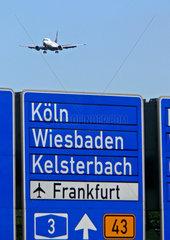 Autobahnschild und Flugzeug ueber der Autobahn am Flughafen Frankfurt