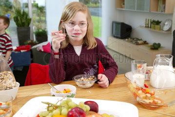 Maedchen isst Muesli mit frischem Obst