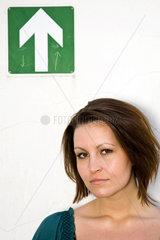 Berlin  Deutschland  ernst blickende junge Frau vor Pfeil-Piktogramm