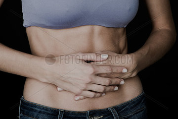 Woman clutching bare stomach with hands