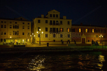 Pedestrians stroll along the edge of the Grand Canal in Venice  Italy  at night