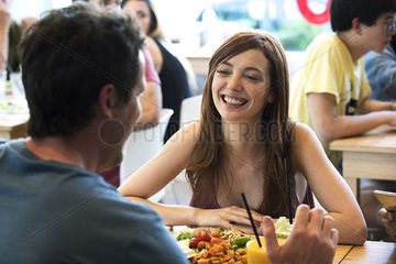 Woman chatting with male friend in restaurant
