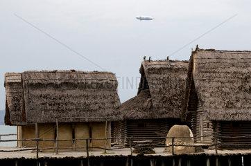 Zeppelin ueber den Pfahlbauten in Unteruhldingen am Bodensee
