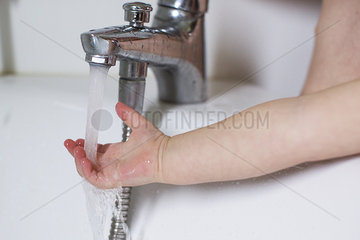 Child's hand testing bath water temperature