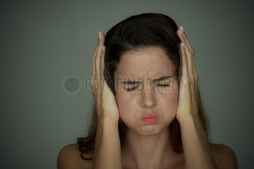 Woman holding hands over ears with eyes closed