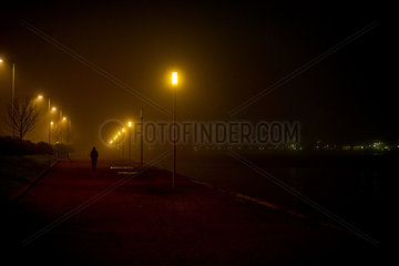 Person walking along deserted waterfront at night