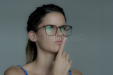 Young woman looking away in thought with finger held to lips