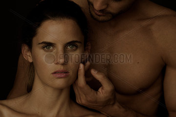 Barechested man caressing woman's cheek as she gazes at the camera