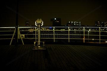 Pay binoculars on waterfront overlook at night