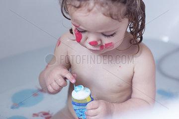 Little girl playing in bathtub