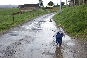 Little girl walking along wet dirt road