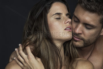 Passionate couple cheek to cheek with eyes closed