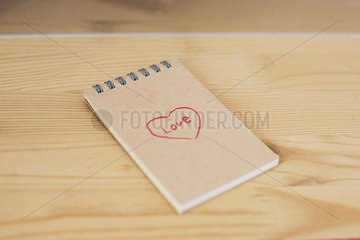 Note pad with heart shape and word love written on cover