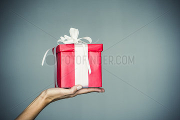 Woman's hand holding wrapped gift