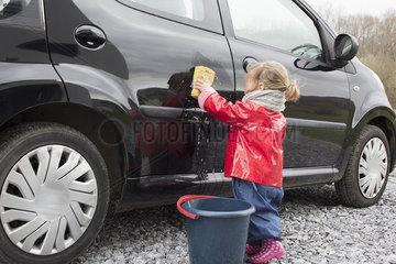 Little girl washing car