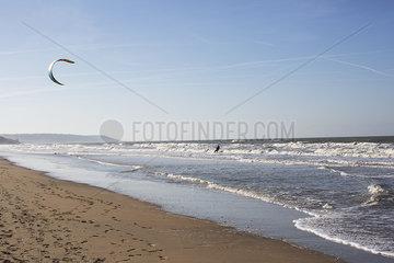 Man paragliding over ocean