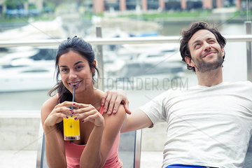 Couple relaxing on patio  woman drinking juice