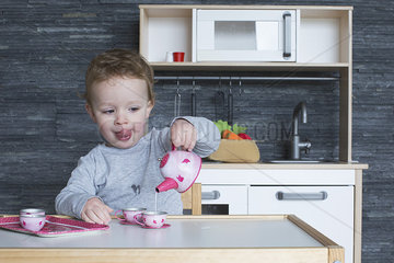 Little girl playing with toy tea set