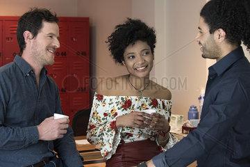 Professor chatting with students in school breakroom