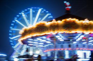 Carousel and ferris wheel illuminated at night
