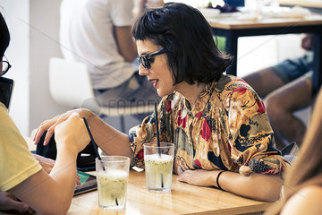 Woman chatting with friends in cafe