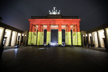 The Brandenburg Gate stands illuminated in the colors of the German flag